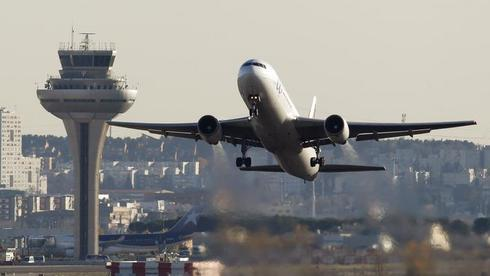 A passenger airplane takes off past the air traffic control tower at Madrid's Barajas airport